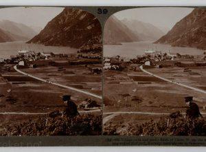 Landsbytak og solfylte enger ved den smale og fjellsteile Sørfjorden (1905)